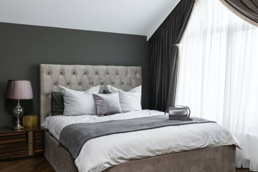 Bed with white and gray sheet and pillows