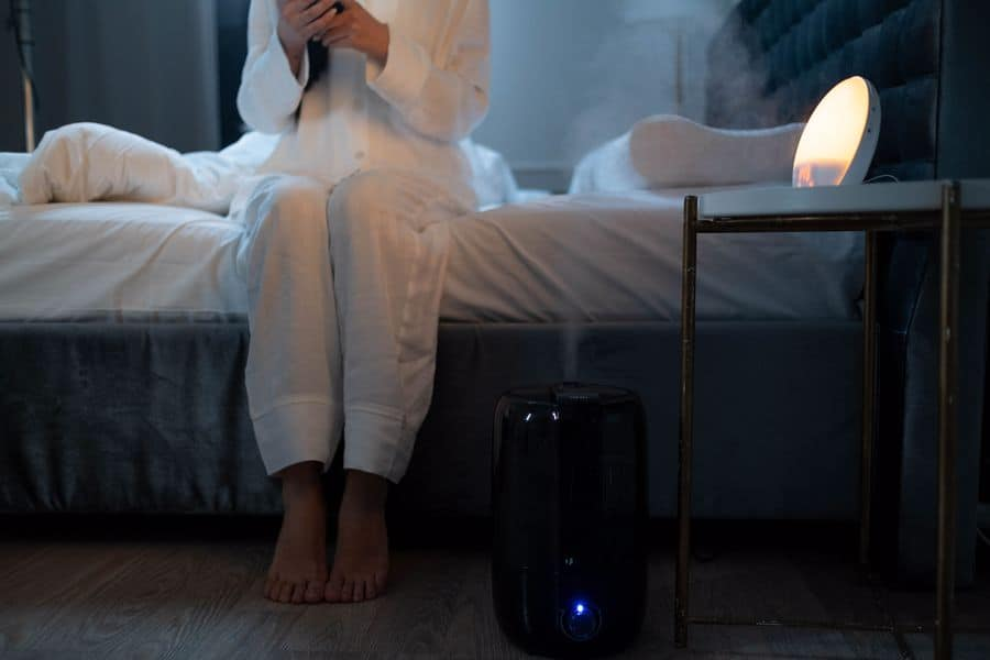 Woman using her humidifier while sitting on her bed