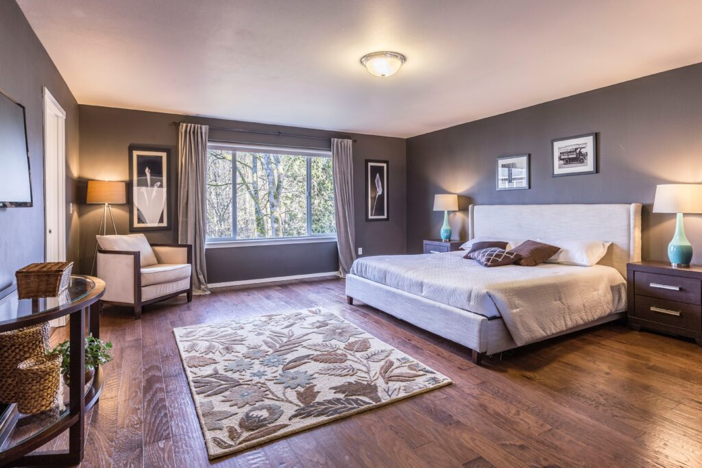 A grey toned living room with a white bed and wood floor