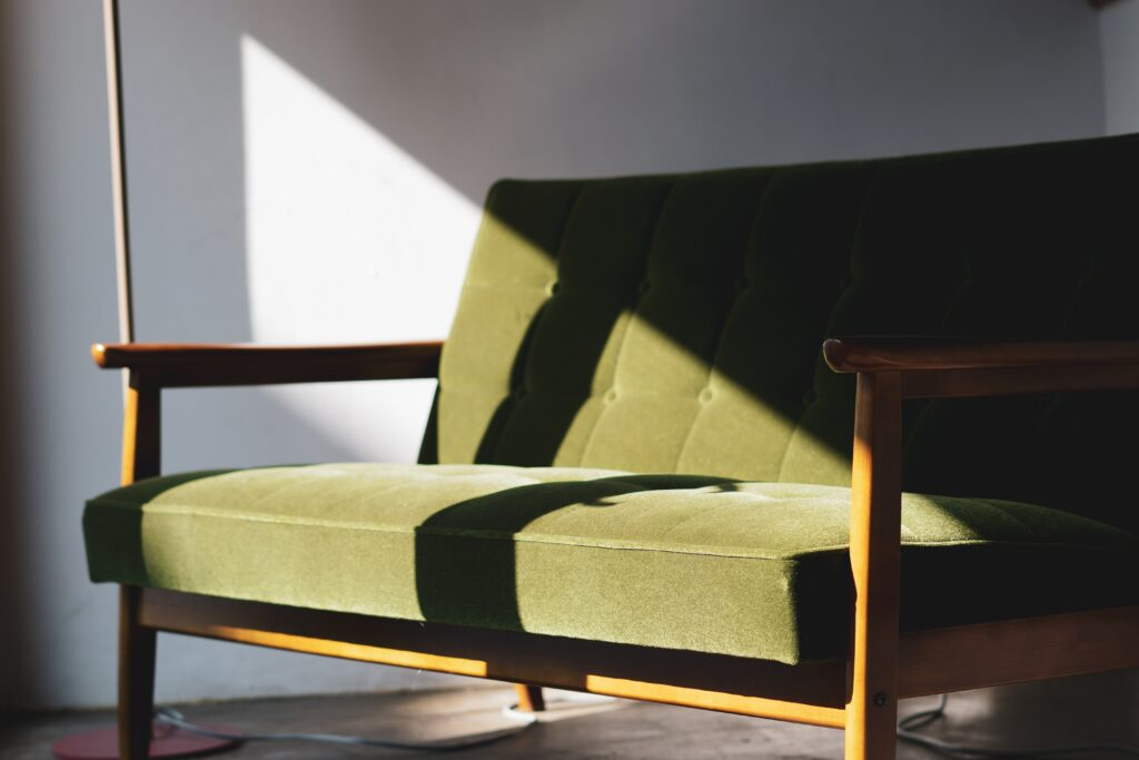 A long green chair with sunlight