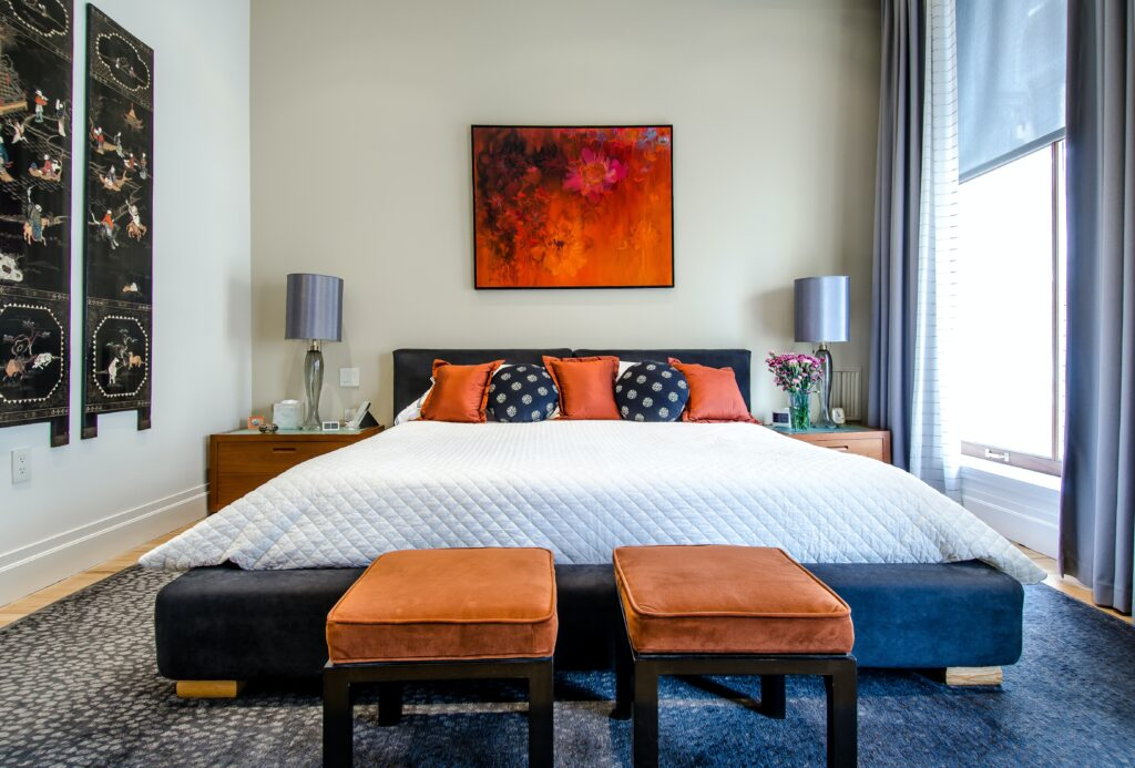 bedroom with orange and black pillows and chairs