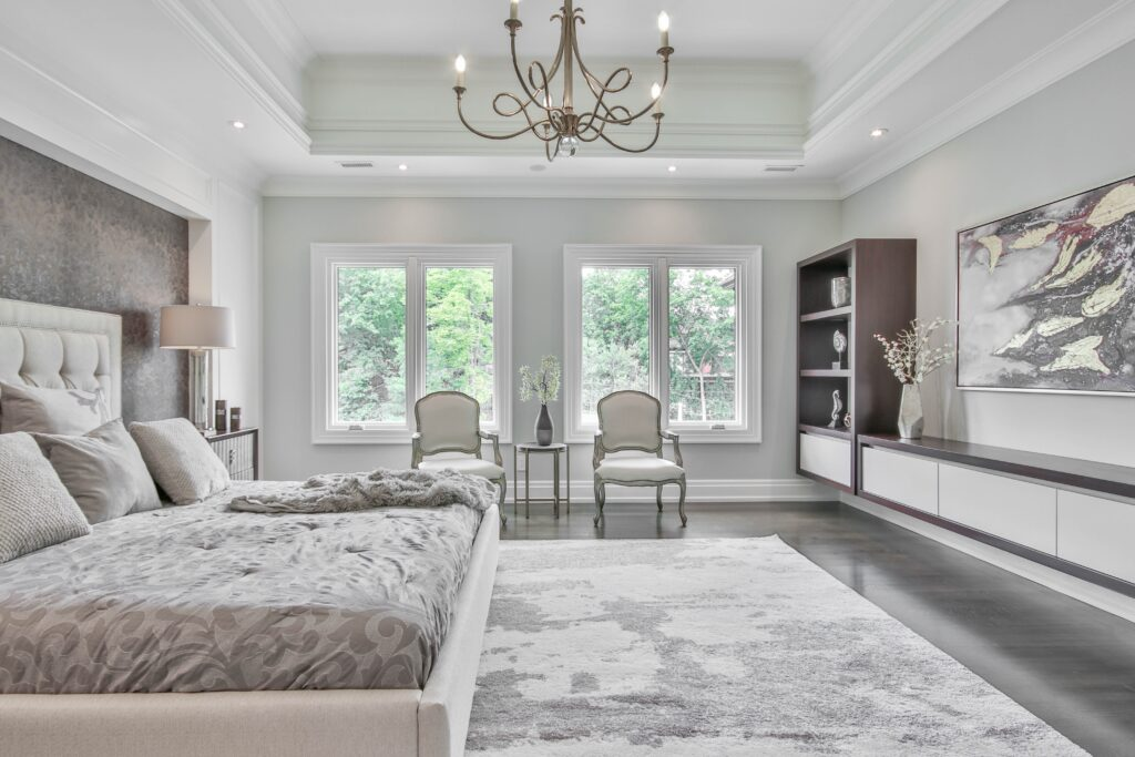 a white and gray toned bedroom with two windows