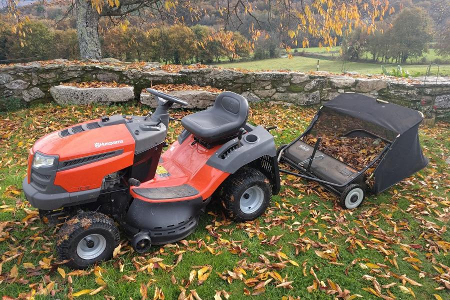 Husqvarna yth22v46 riding lawn mower collecting dried leaves in backyard