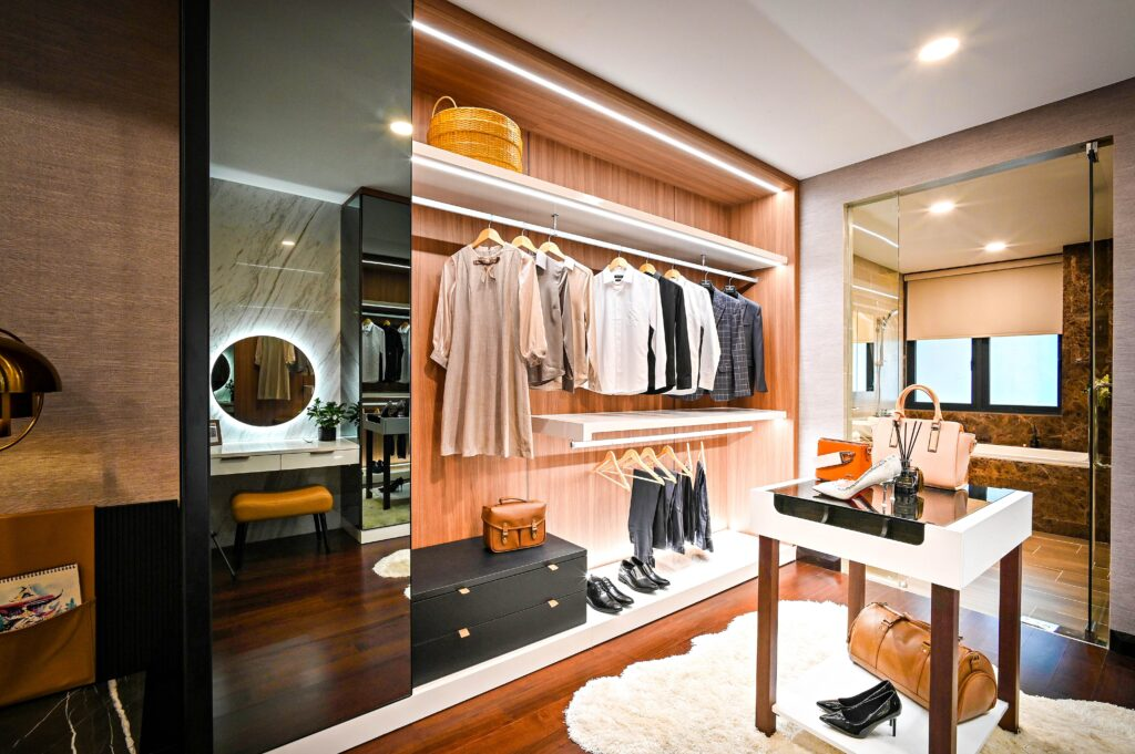 An open closet with mirror and clothes