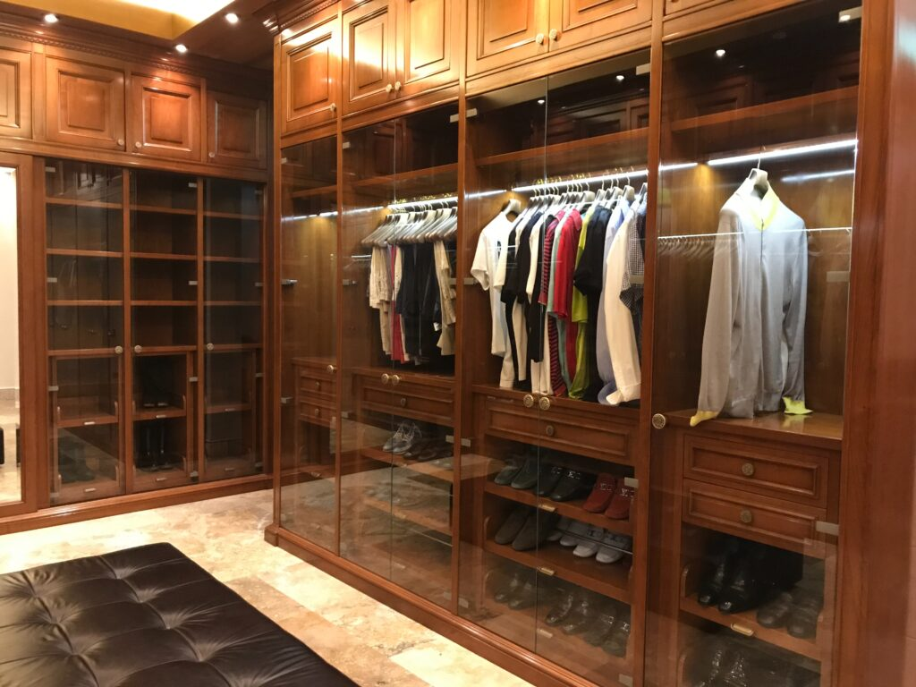 A mirrored closet with clothes and shoes