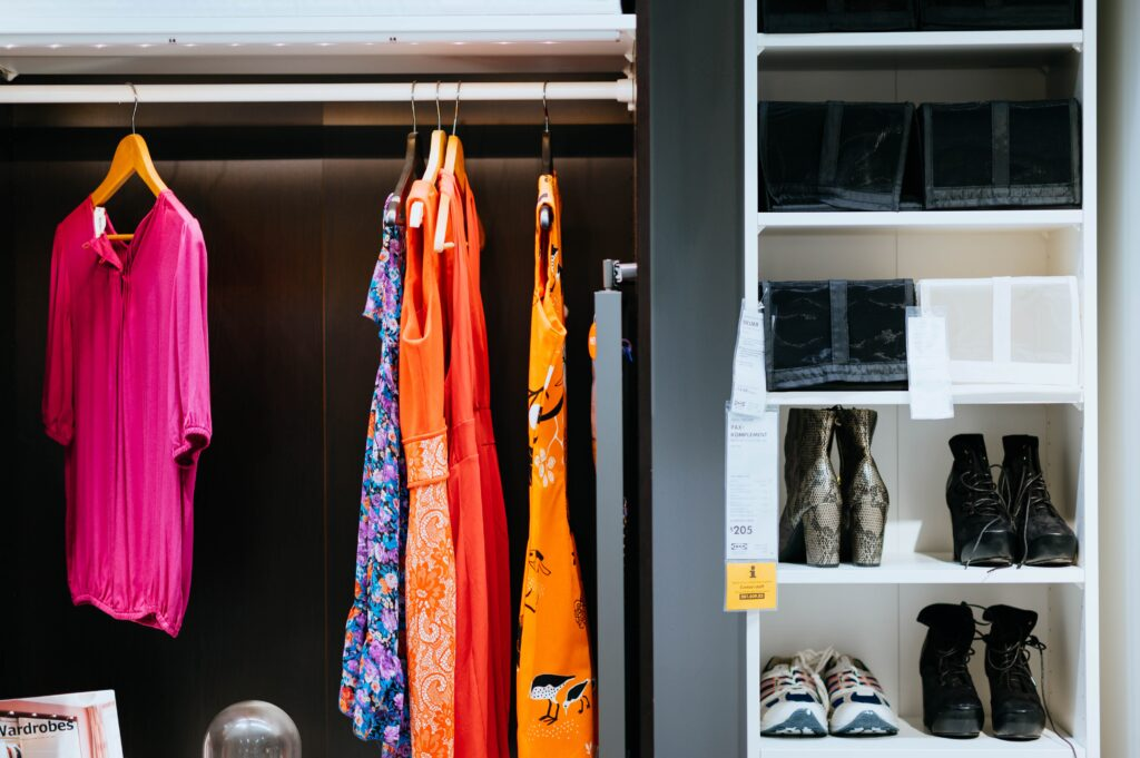 A closet with a few clothes and shoes