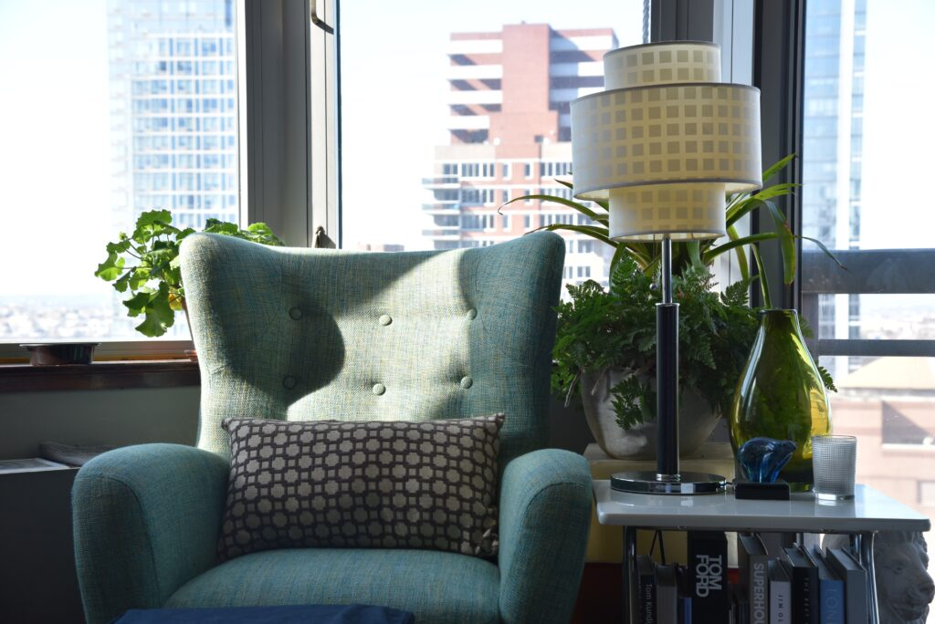 A chair with a lamp near the window