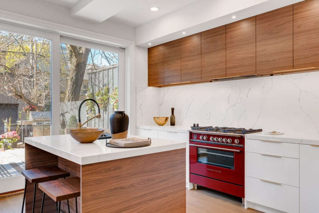 A white toned kitchen and dining area with wooden cabinets