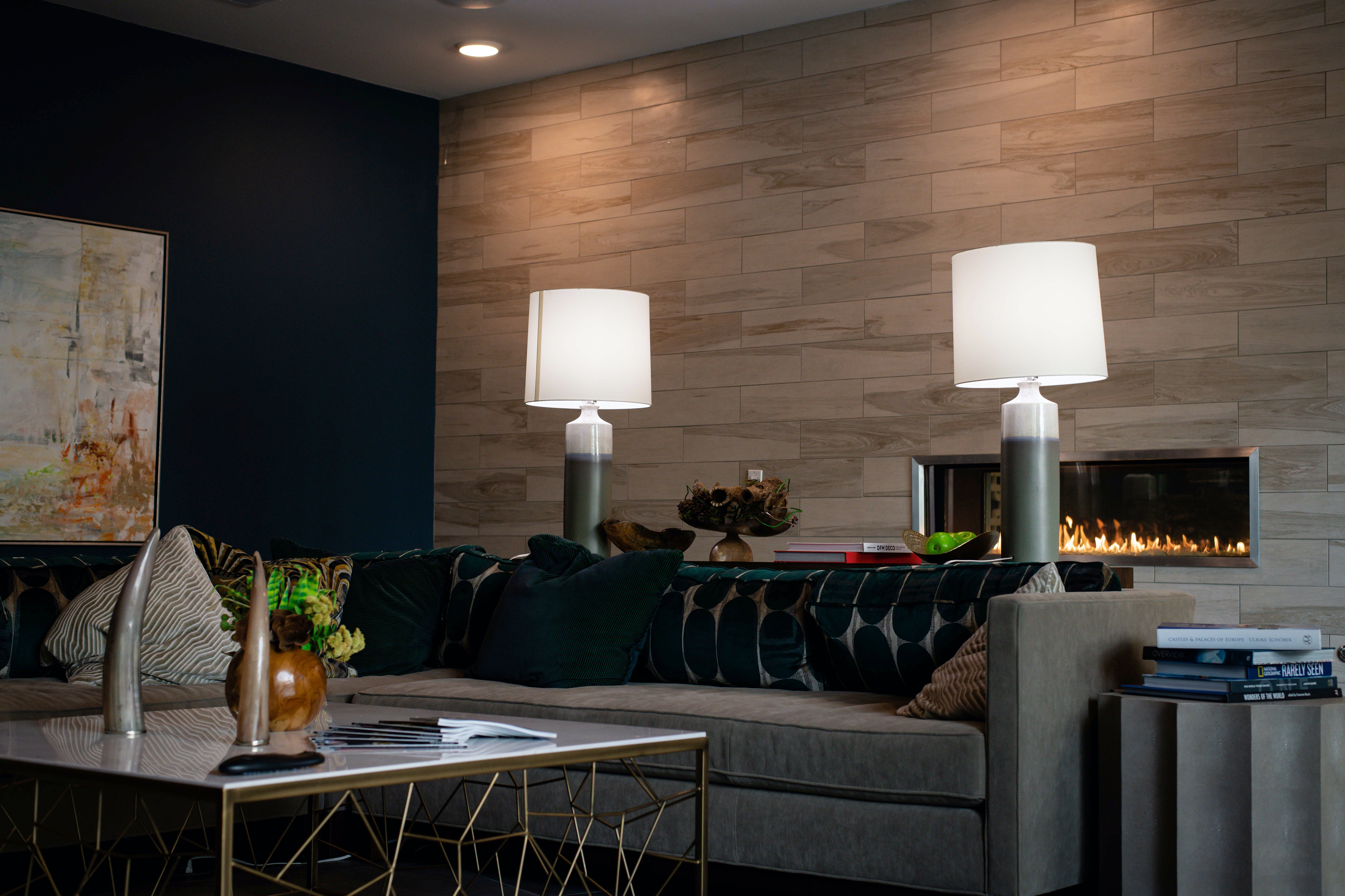 A dark blue toned living room with lamps and fireplace