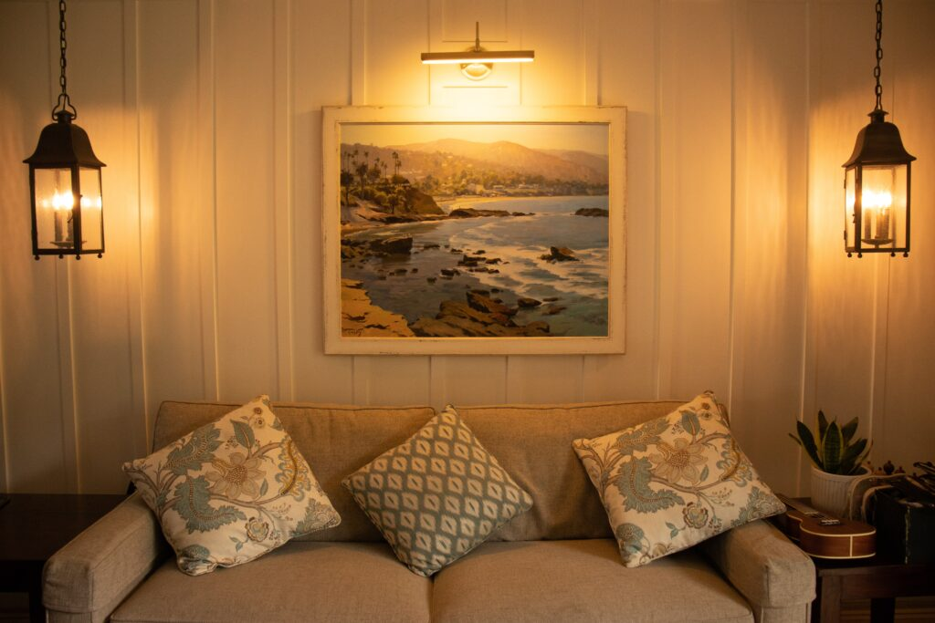 A living room with a painting and a sofa near the lights
