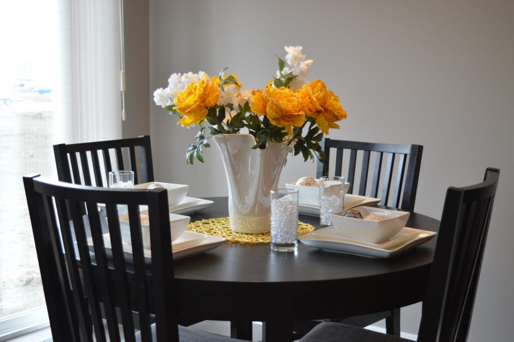 A dinner table with flowers on the center