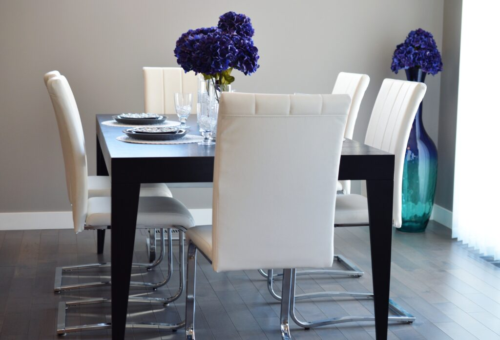 A dinner table with white chairs and purple flowers