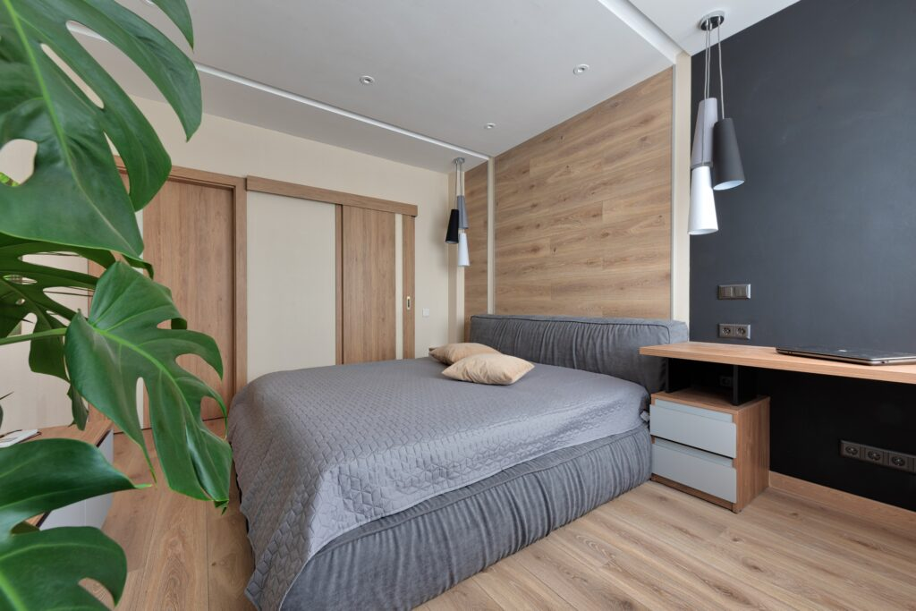A bedroom with a gray bed