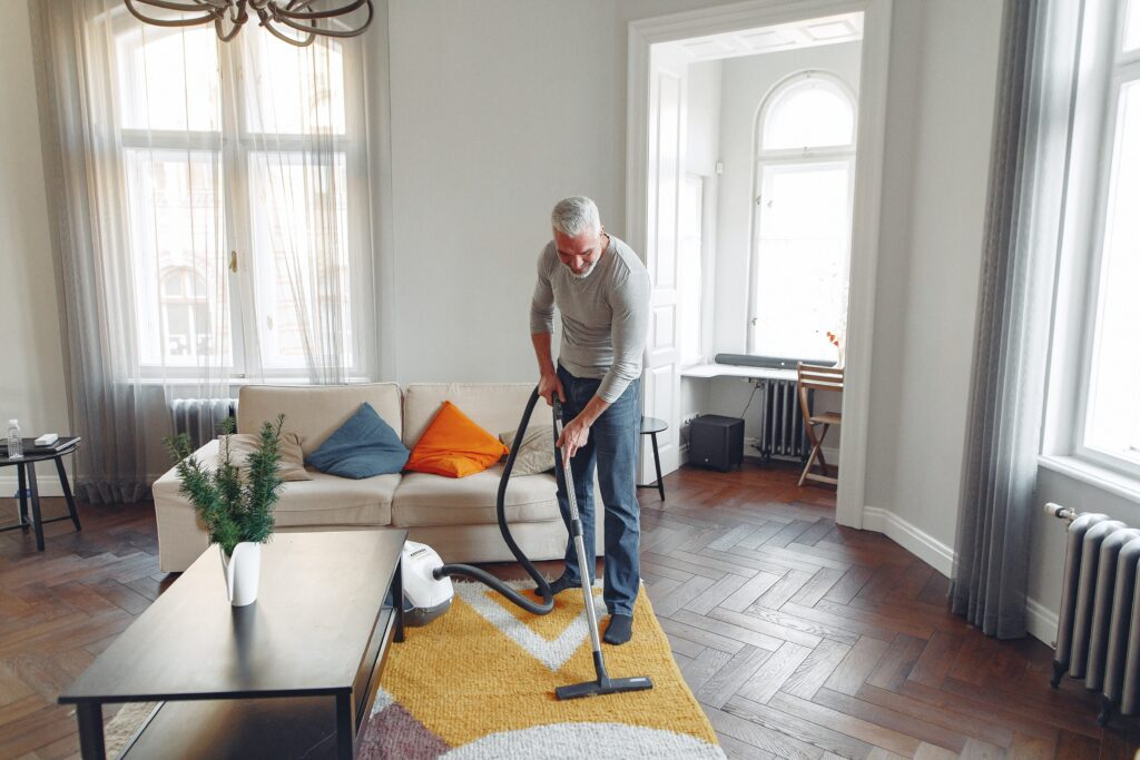 A man cleaning a carpet with a vacuum cleaner