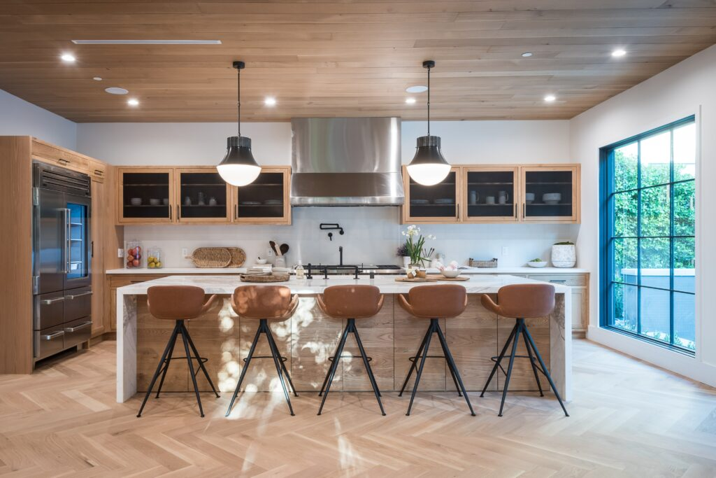 A brown toned kitchen area with chairs, cabinets and lights