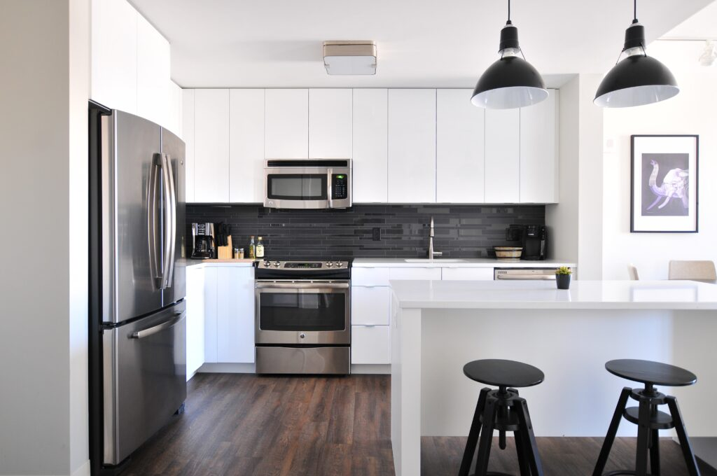 A black and white toned kitchen area with chairs, cabinets and lights