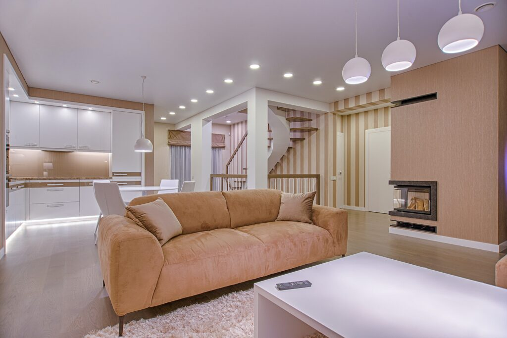 A big brown sofa in the living room with lights