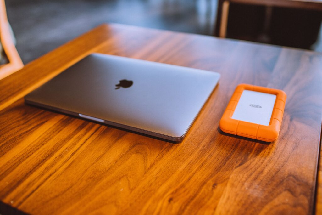 A shiny wooden table with a laptop
