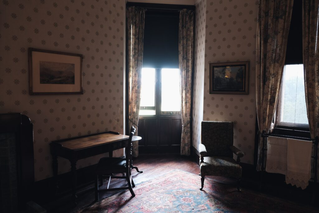 A room with chairs and simple wallpapers on wall