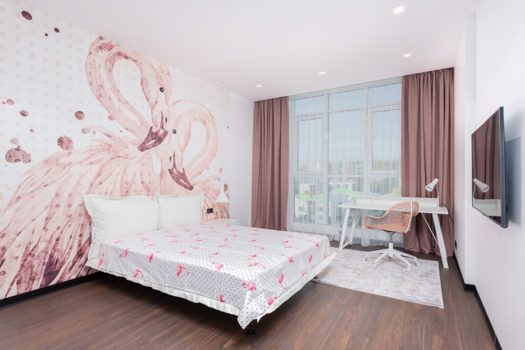 Bedroom with bed sheet on bed and flamingo painting on wall