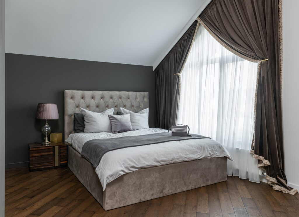 An open windowed bedroom with bed sheets and pillows