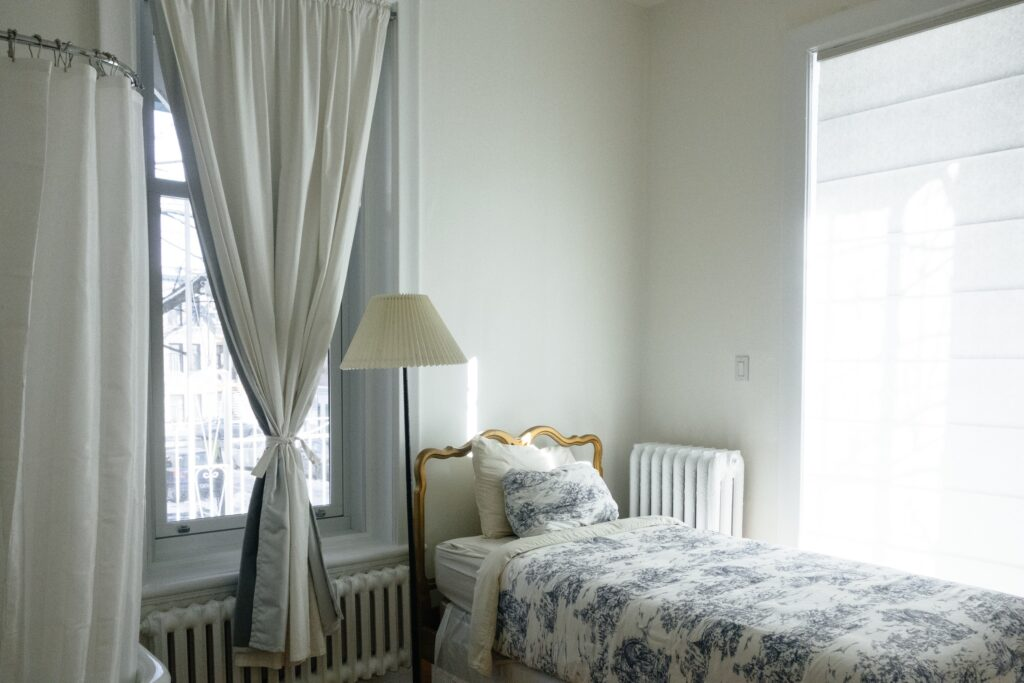 A white toned bedroom with bright windows and blue marked bed sheets