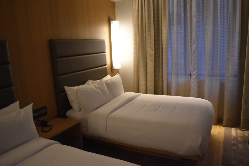 A bedroom with white bed sheets and pillows