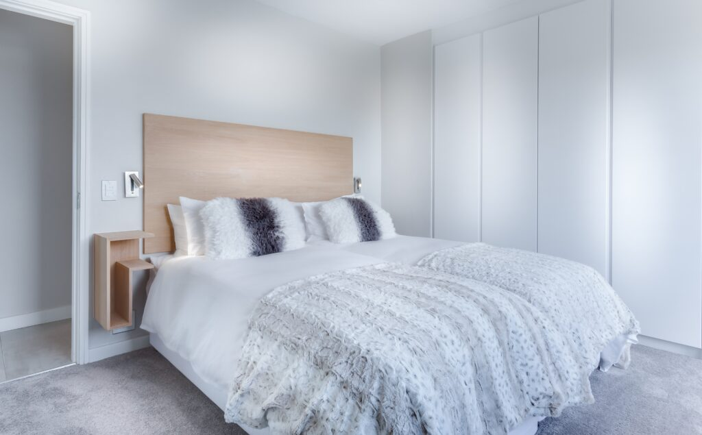 A white toned bedroom with pillows and wide bed sheet