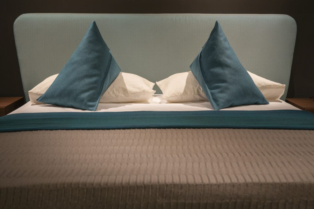 A gray and brown toned bed furniture with blue pillows and bed sheet