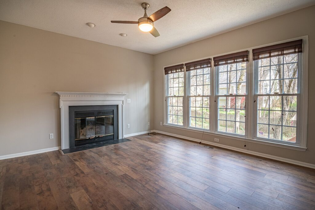 An empty room with four windows and a ceiling fan