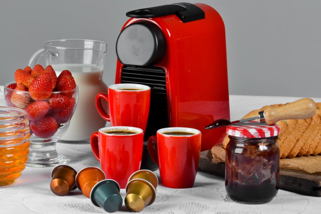A red coffee maker with red mugs filled with coffee