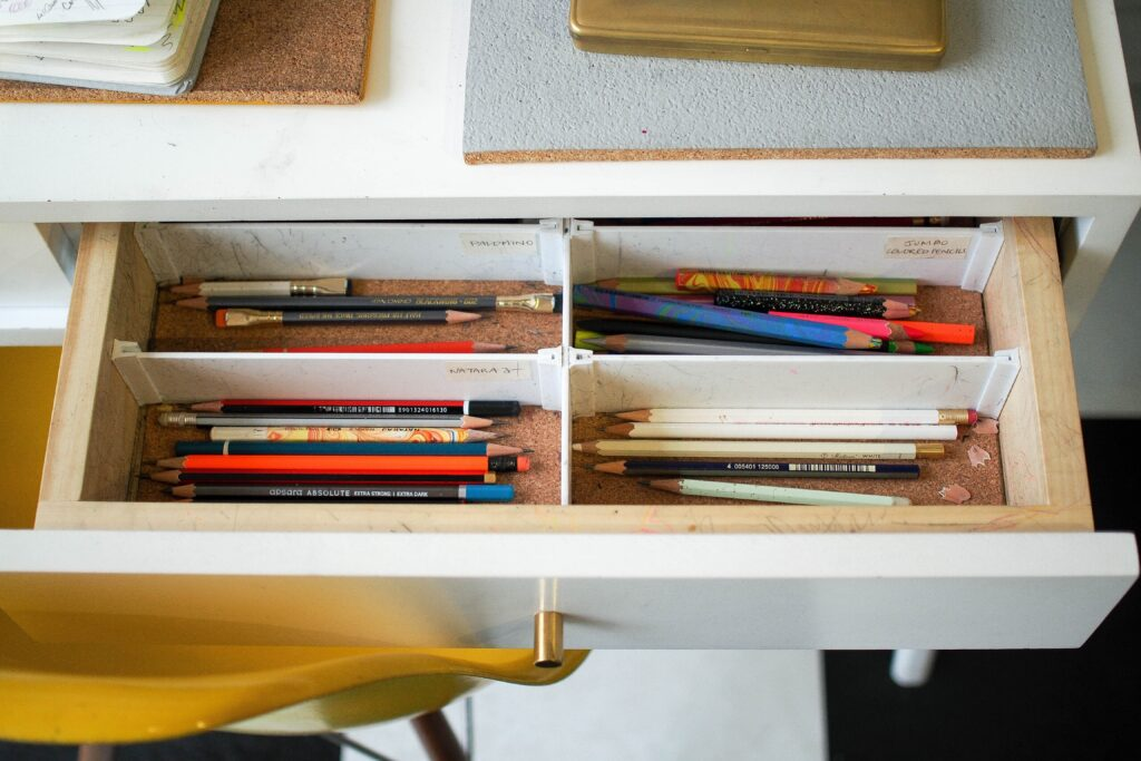 An open drawer with colored pencils