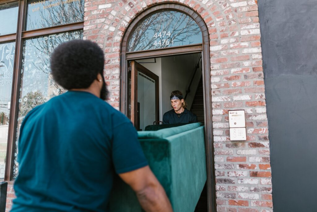 Two persons moving a couch in a narrow hallway