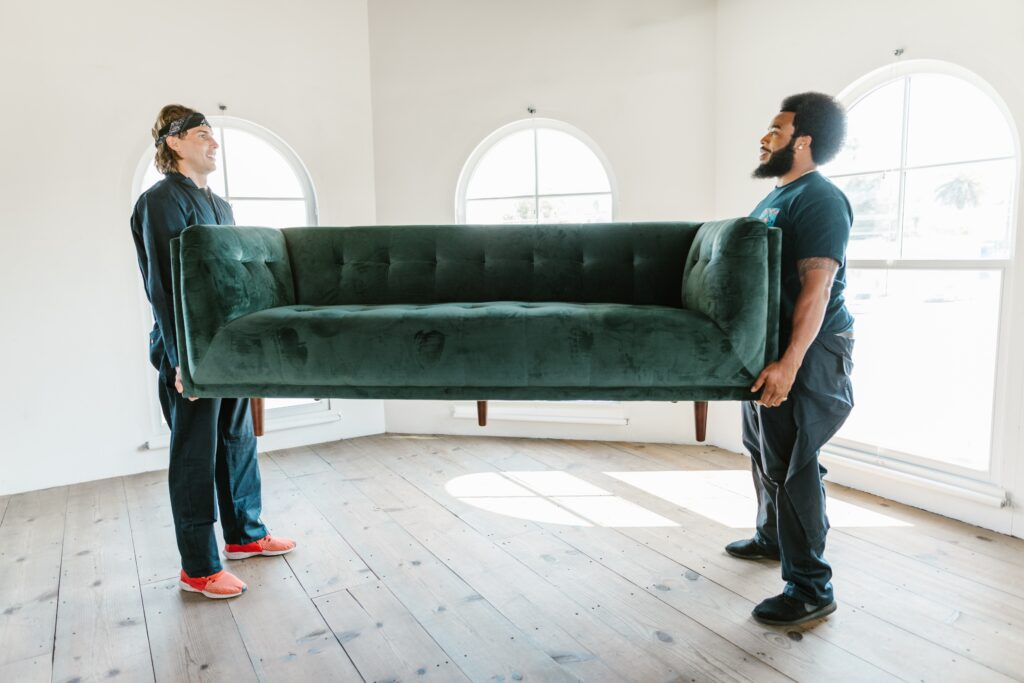 Two people carrying and moving a blue green sofa
