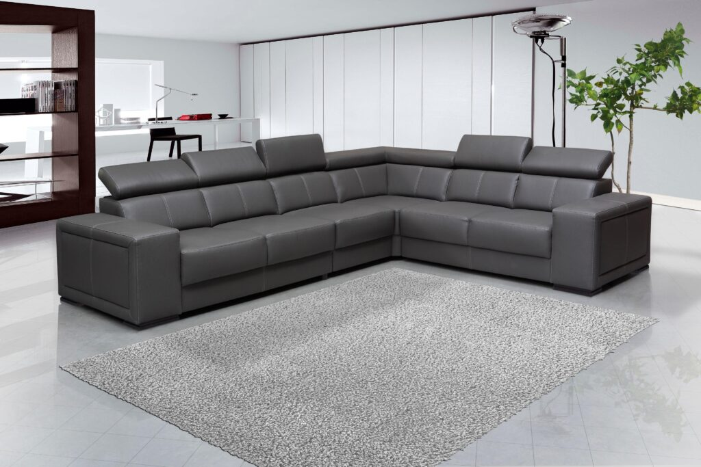 A gray toned sectional sofa with a rug