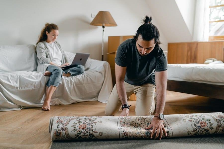 Man arranging a rug