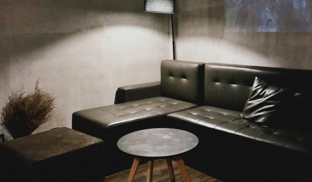 Black leather sectional couch with a floor lamp