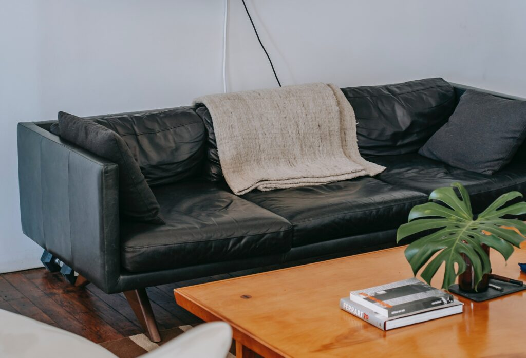 A black leather couch with a wooden table in front