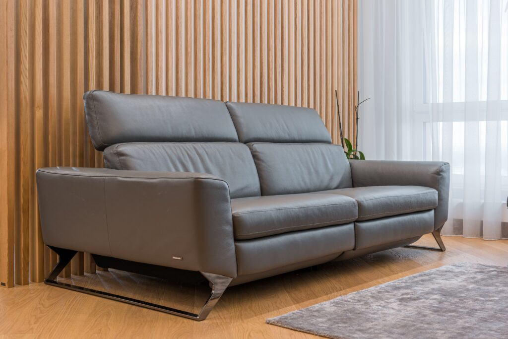 A gray leather couch on hardwood floor