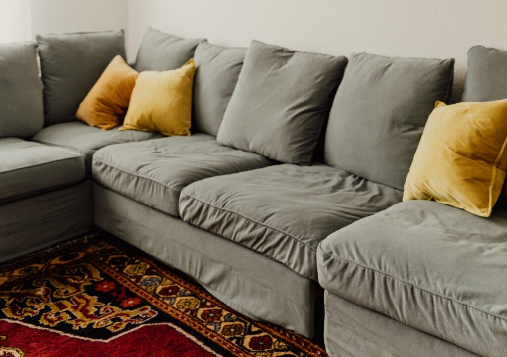 A gray sectional sofa with gray and yellow pillows