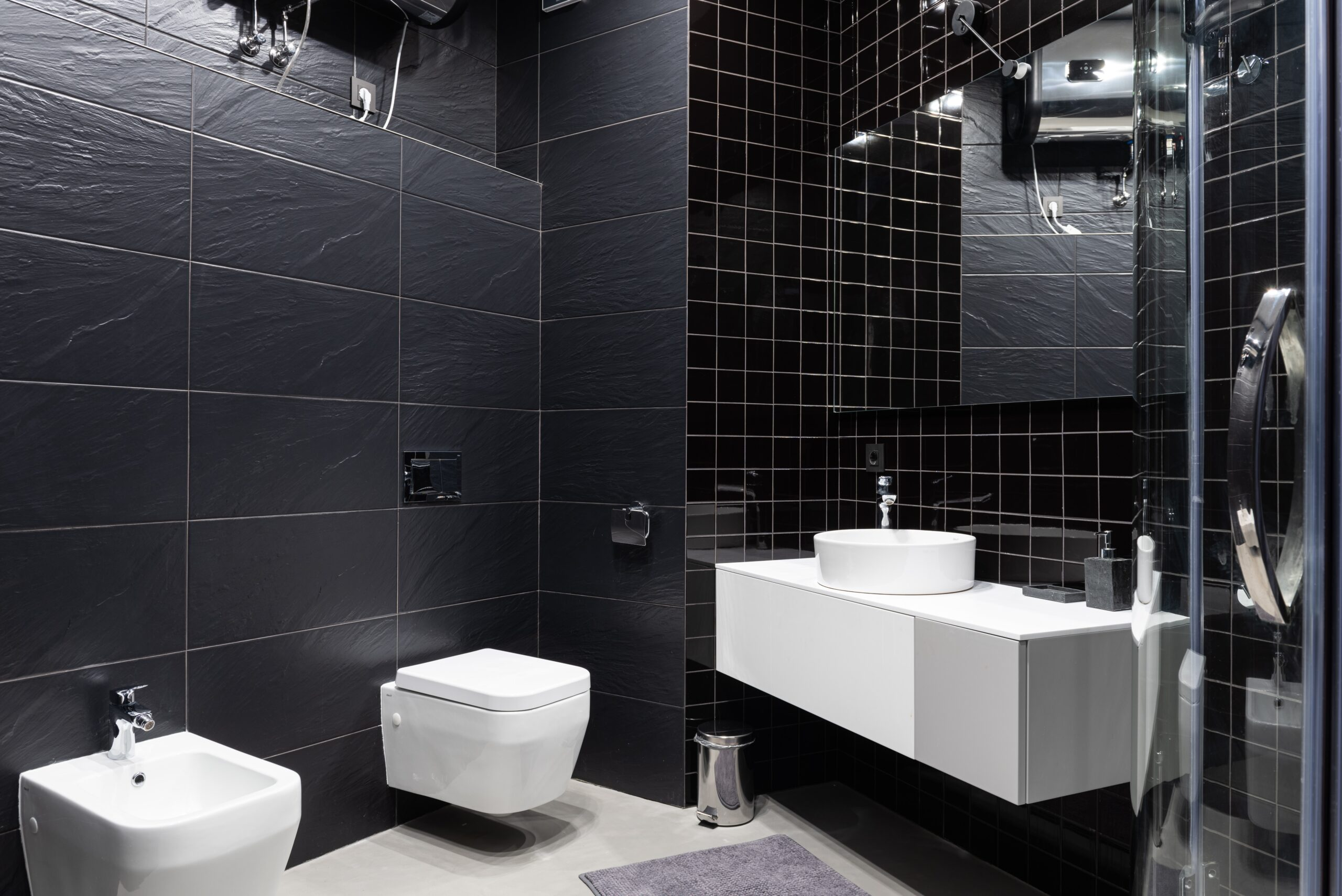 A bathroom with white ceramics and black tiles