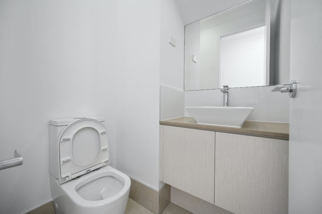 A bathroom with a toilet bowl and a sink with cabinets and a mirror