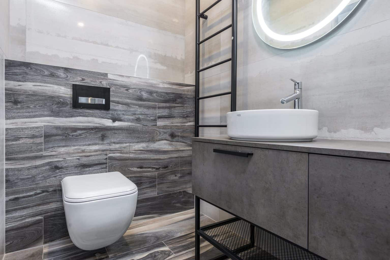 A bathroom with white ceramic sink and toilet