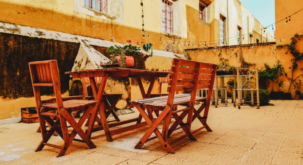 Outdoor wooden chairs and wooden tables in a hot weather