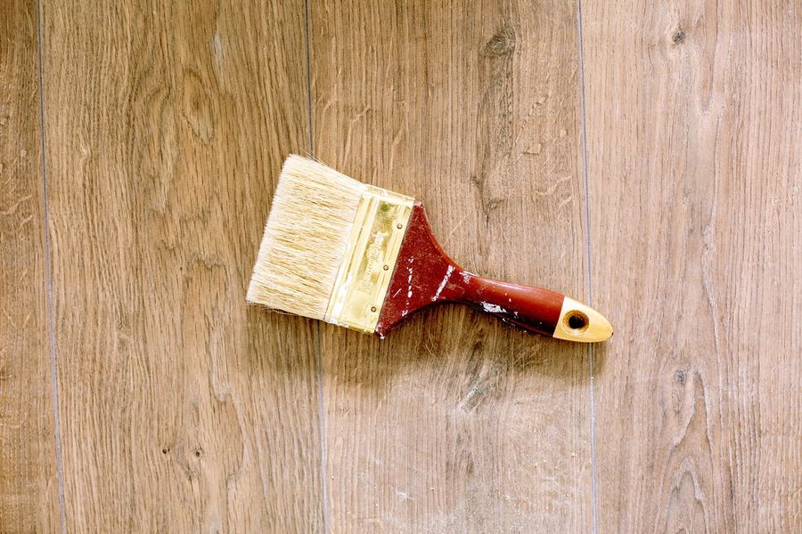Paint brush on top of stained wood furniture