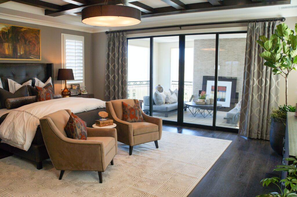 A master bedroom with brown chairs and an patio furniture near the window