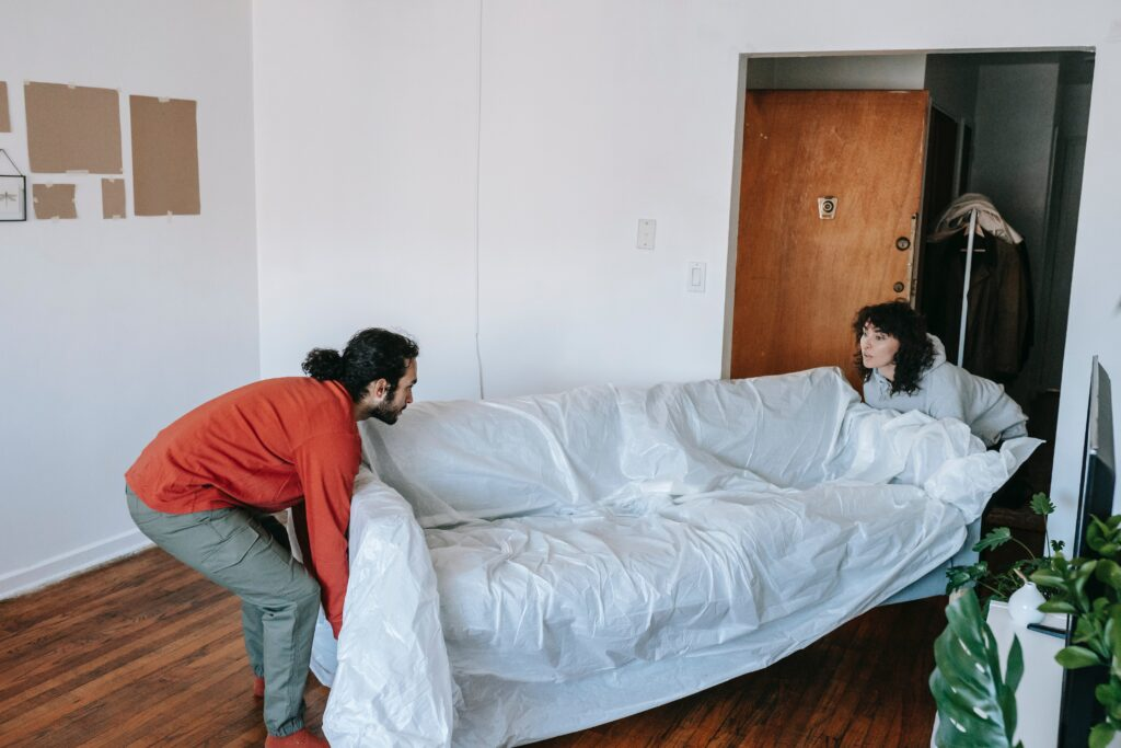 Two people moving a couch through a door to a room