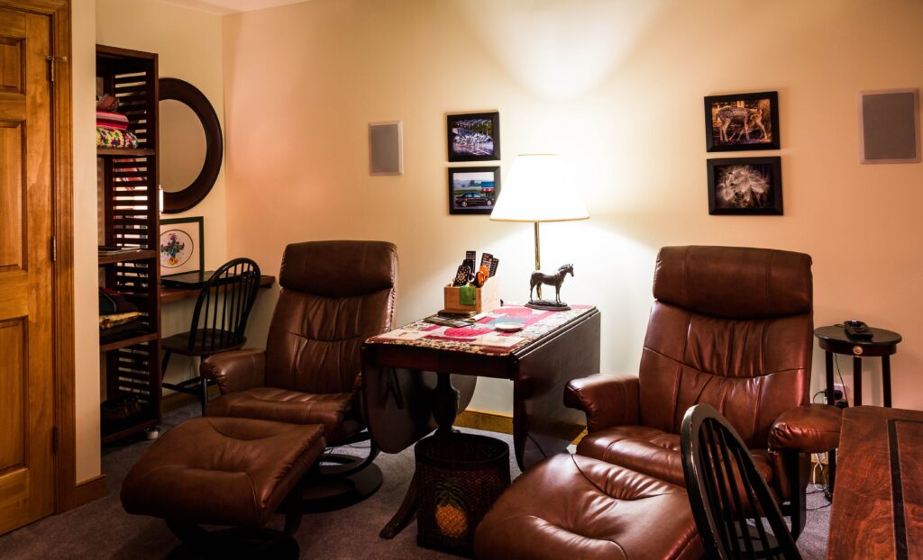 Two recliner chairs in a room with leg rest and a bright light