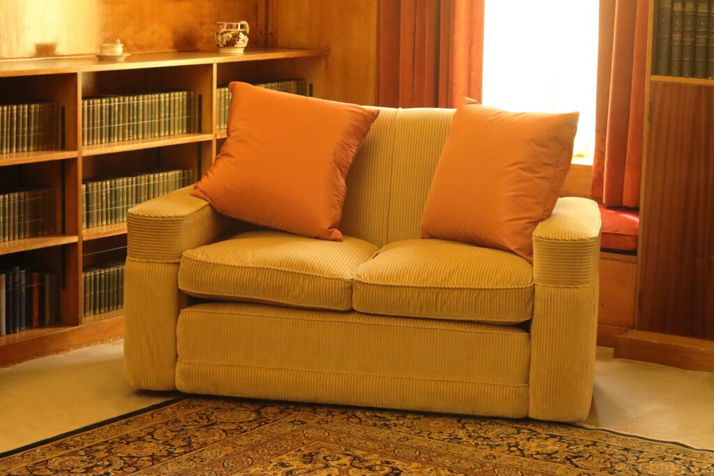 A yellow cozy couch near the window with orange pillows