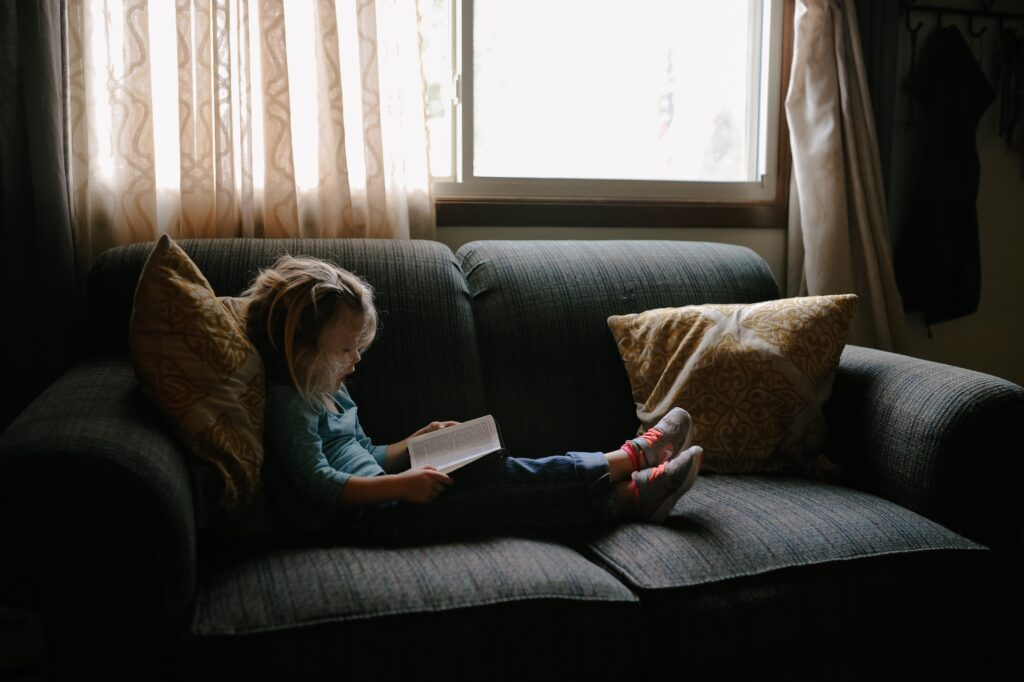 A child reading a book on a black couch near the window